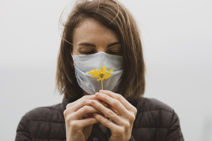 Female mourner wearing a face mask and holding a flower