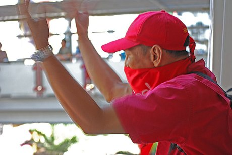 "A ""red shirt"" anti-government protester motions to his friends to join him inside a Bangkok rail station."
