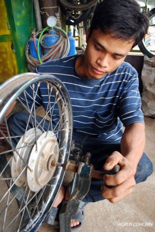 Young men learn how to repair motorbikes in Poi Pet, Cambodia, a border community at risk for Child Trafficking.
