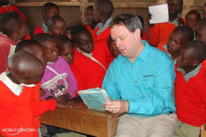 World Concern President Dave Eller spends time reading to Maasai boys in Kenya. World Concern works with the Maasai to provide many aspects of sustainable humanitarian aid.