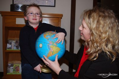 Jonathon points out Haiti on a globe as Heidi Williams with World Concern watches.