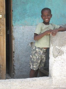 A Hatian boy outisde his newly repaired home.