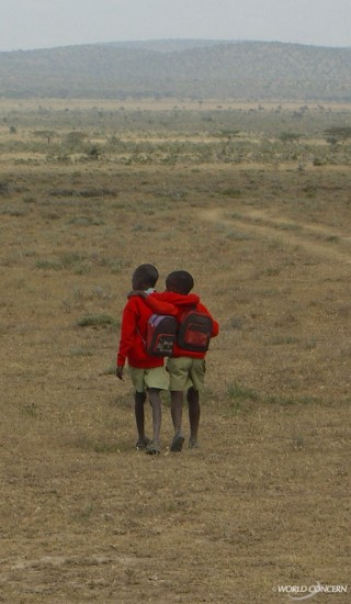 Two Kenyan students walk home from school.