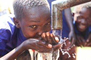 A boy in South Sudan drinks clean water from a well.