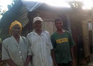 Mr. Maxi and family members outside their one-room shelter.