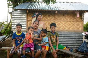 A family in the Philippines outside their newly constructed home. Photo by Miguel Samper, courtesy of Medair.
