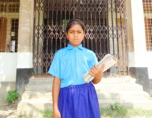 Mitu, now 8 years old, in front of her school.