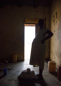 A silhouetted pregnant woman rests at an IDP site.