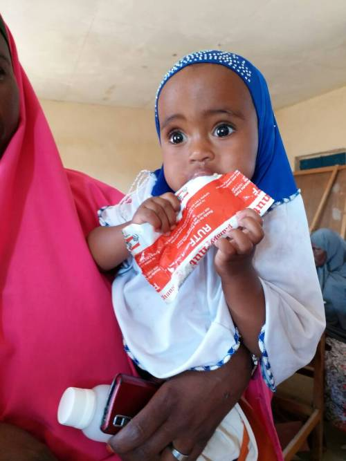 young girl eats nutripacket in Somalia