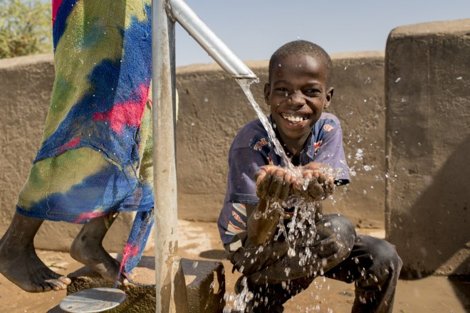 a smiling boy holding out his hands for water