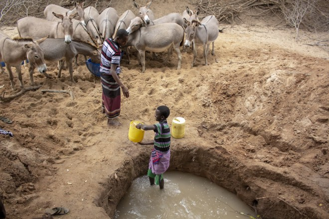 two brothers fetch water from a makeshift well