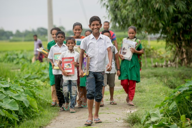 a boy walks with other children on a path to school