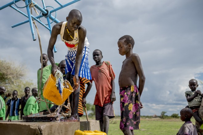 children gather water in a yellow bucket from a village well