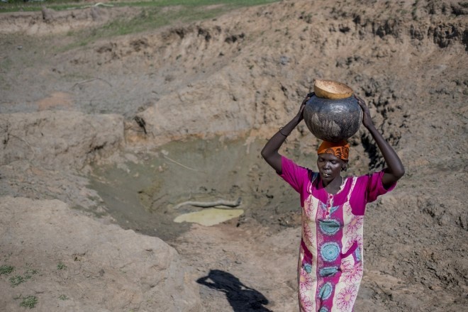a woman carries a jar of water on her head next to a small pond