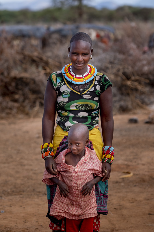 a mom standing with her arms around her son