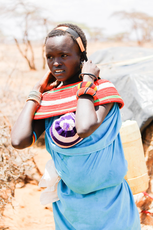 a Kenyan woman holds a water jug with a strap on her forehead