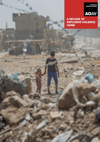 A little boy and little girl seen through barbed wire standing in a background of rubble.