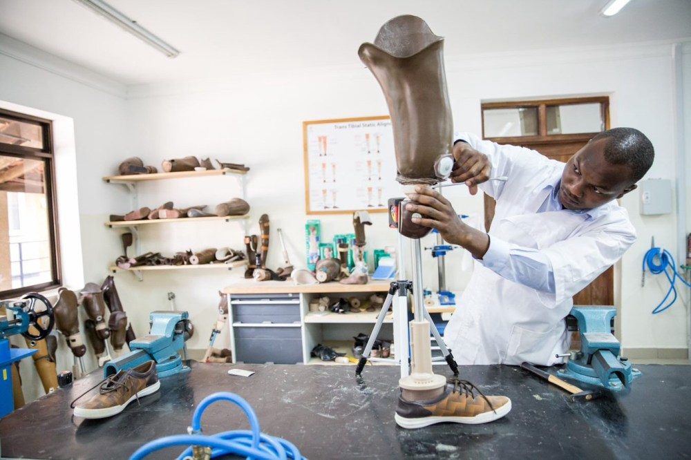 A man works to complete a lower-limb prosthetic in a CCBRT lab in Tanzania.