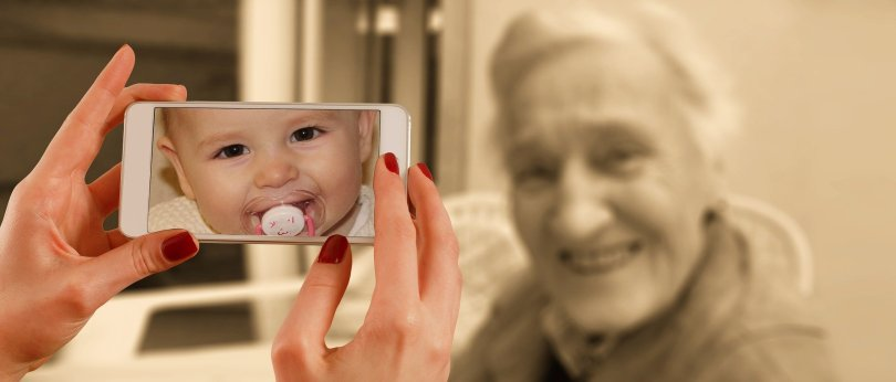 smartphone taking picture of old woman with screen showing a baby