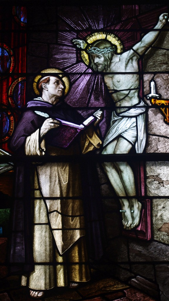 Stained glass window featuring St Thomas Aquinas with Jesus on the cross