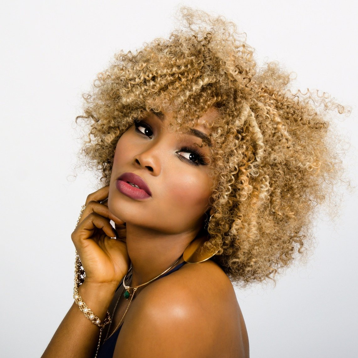 mixed race woman with blond curly hair