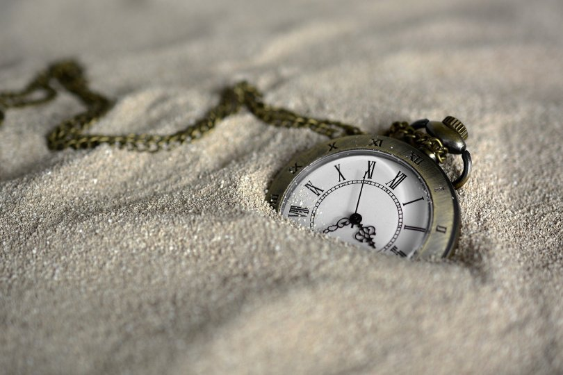 pocket watch semi buried in sand
