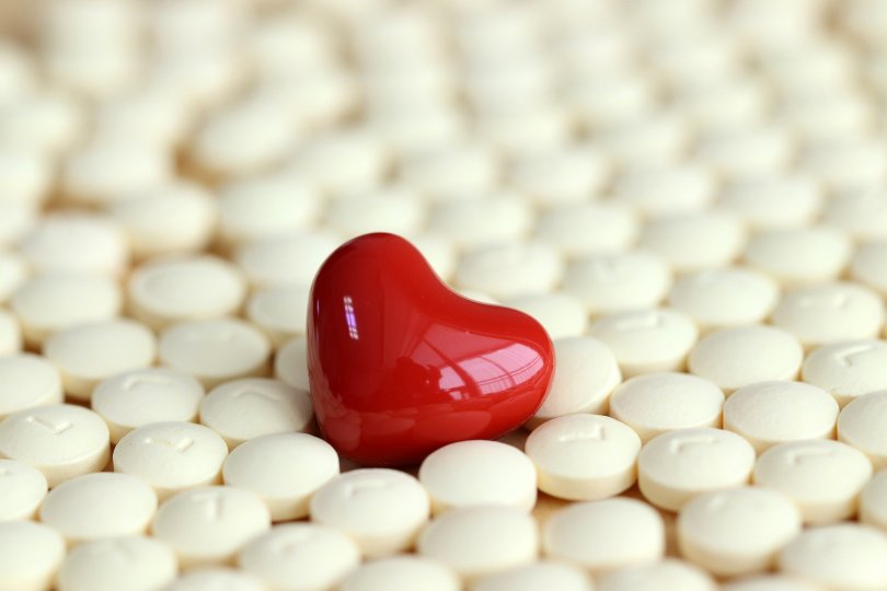 red heart shaped pill in amongst lots of round white pills