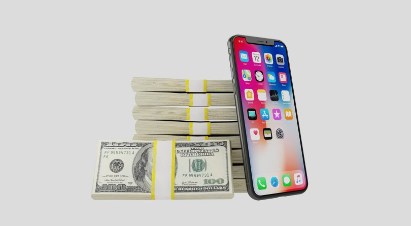 Iphone next to piles of dollars