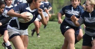 female rugby player running with the ball