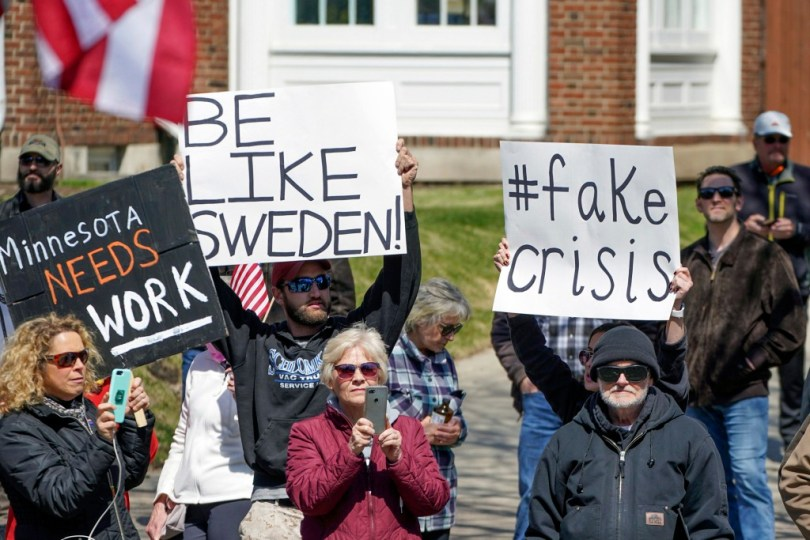 anti lockdown protesters holding be like sweden placard