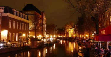 Amsterdam at night with outdoor diners by canalsideoor