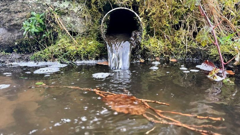 sewage outflow pipe discharging into a river