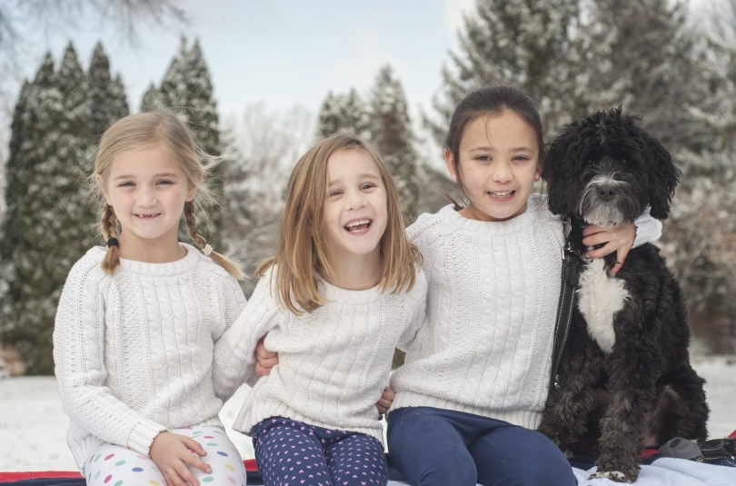 3 young girls sat with a dog in snowy landscape