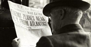 Sanomalehteä lukeva mies.