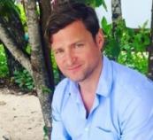 Richard wearing blue shirt, sitting by tree