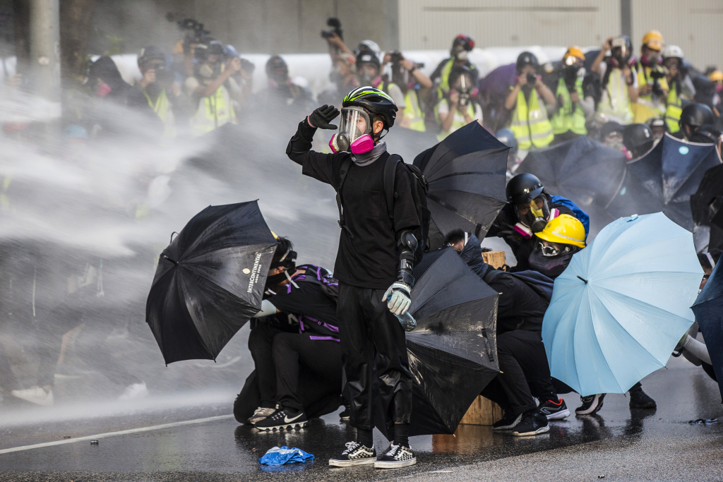 A pro-democracy protester reacts as police fire water cannons outside the government headquarters in Hong Kong on September 15, 2019. - Hong Kong riot police fired tear gas and water cannons on September 15 at hardcore pro-democracy protesters hurling rocks and petrol bombs, in a return to the political chaos plaguing the city.