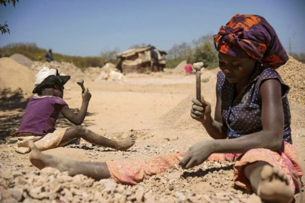 A Child And A Woman Break Rocks Extracted From A Cobalt Mine At A Copper Quarry And Cobalt Pit In Lubumbashi, Congo
