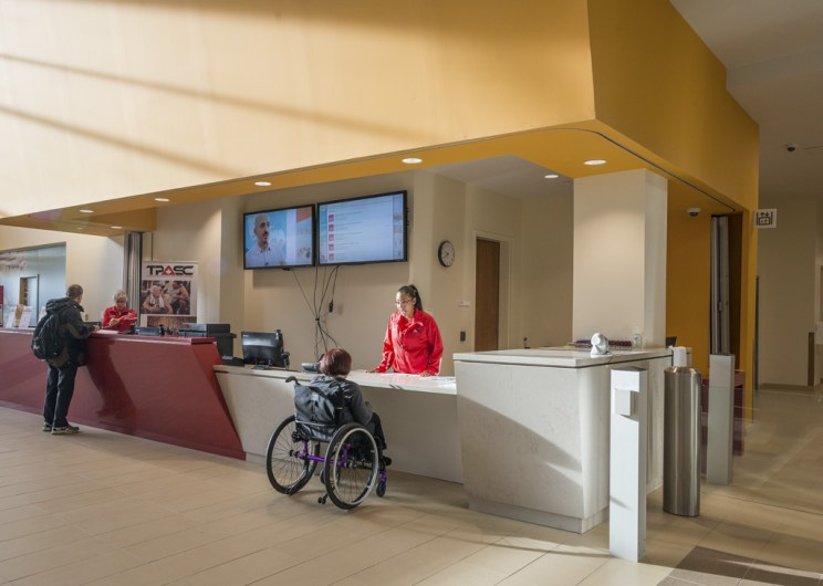 a woman in a mobility device speaks to someone at the lowered portion of a customer service desk