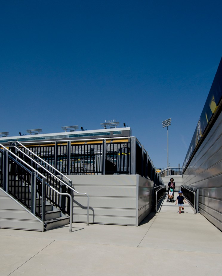 a woman pushes a stroller down a ramp at a sports stadium as her older child runs ahead