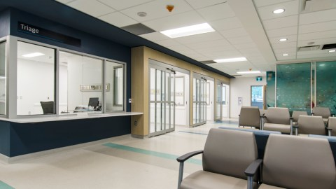 rendering of the emergency room waiting area and triage intake desk of Joseph Brant Hospital, featuring automatic sliding doors, generous clearances, and a lowered reception desk with knee clearance