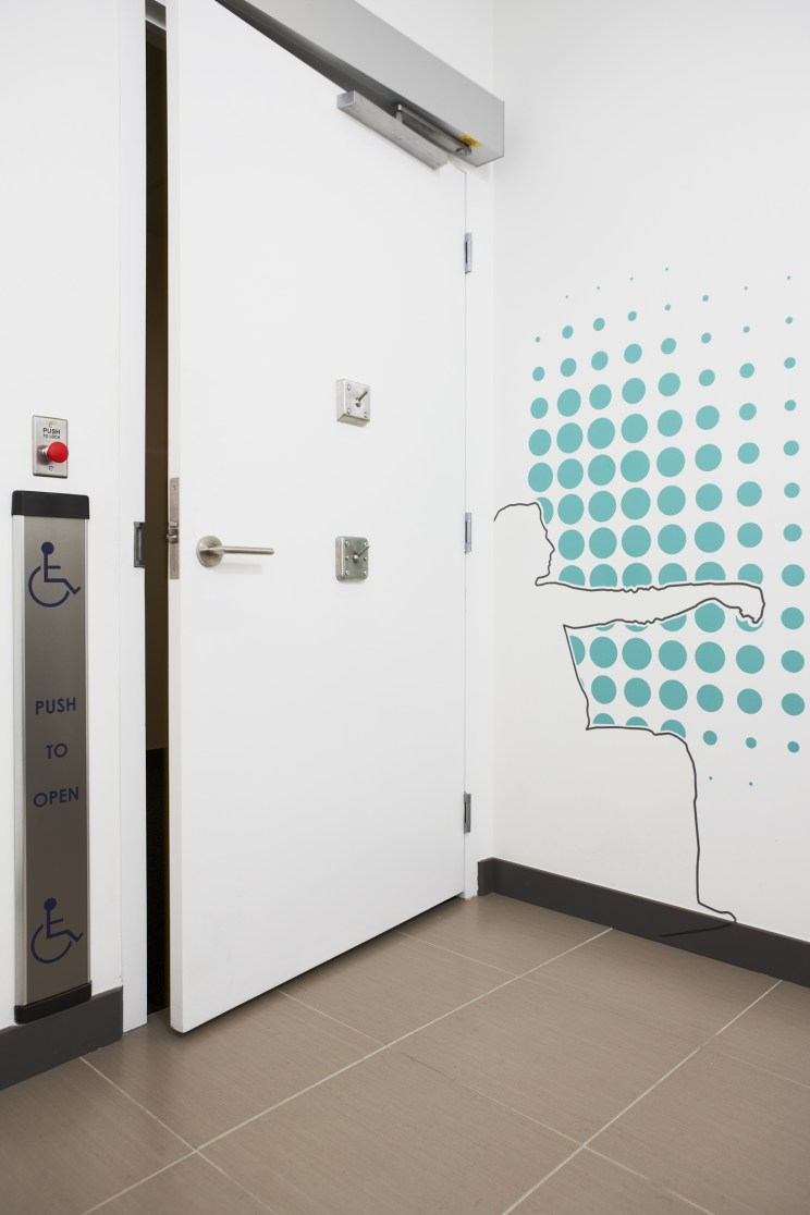 inside a universal washroom, showing lowered coat hook, push door operator button, and a wall decal of a person in a wheelchair