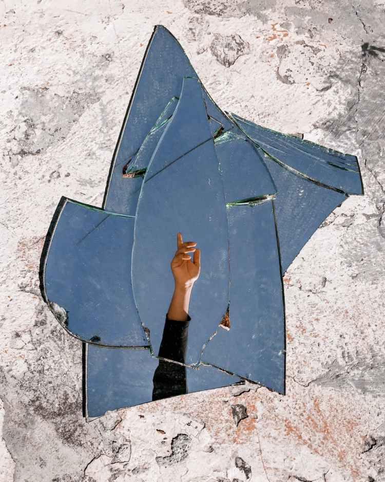 crop person hand in broken mirror