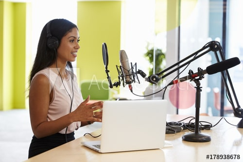 young mixed race women recording a podcast in a studio.