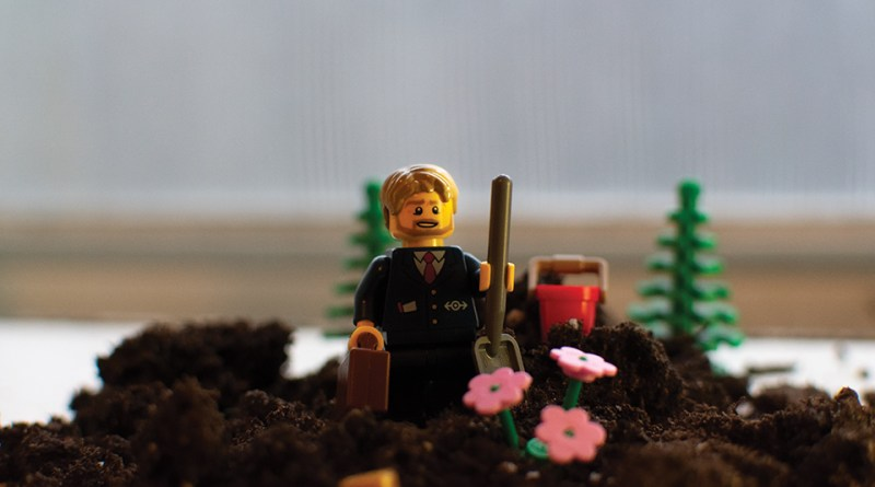 Picture of Lego figure in suit with briefcase holding shovel standing on soil. Lego flowers are blooming out of them.