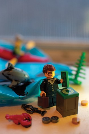 Lego figure holding briefcase in one hand and money in the other. There is a dolphin, lobster and fish covered in oil in the background.