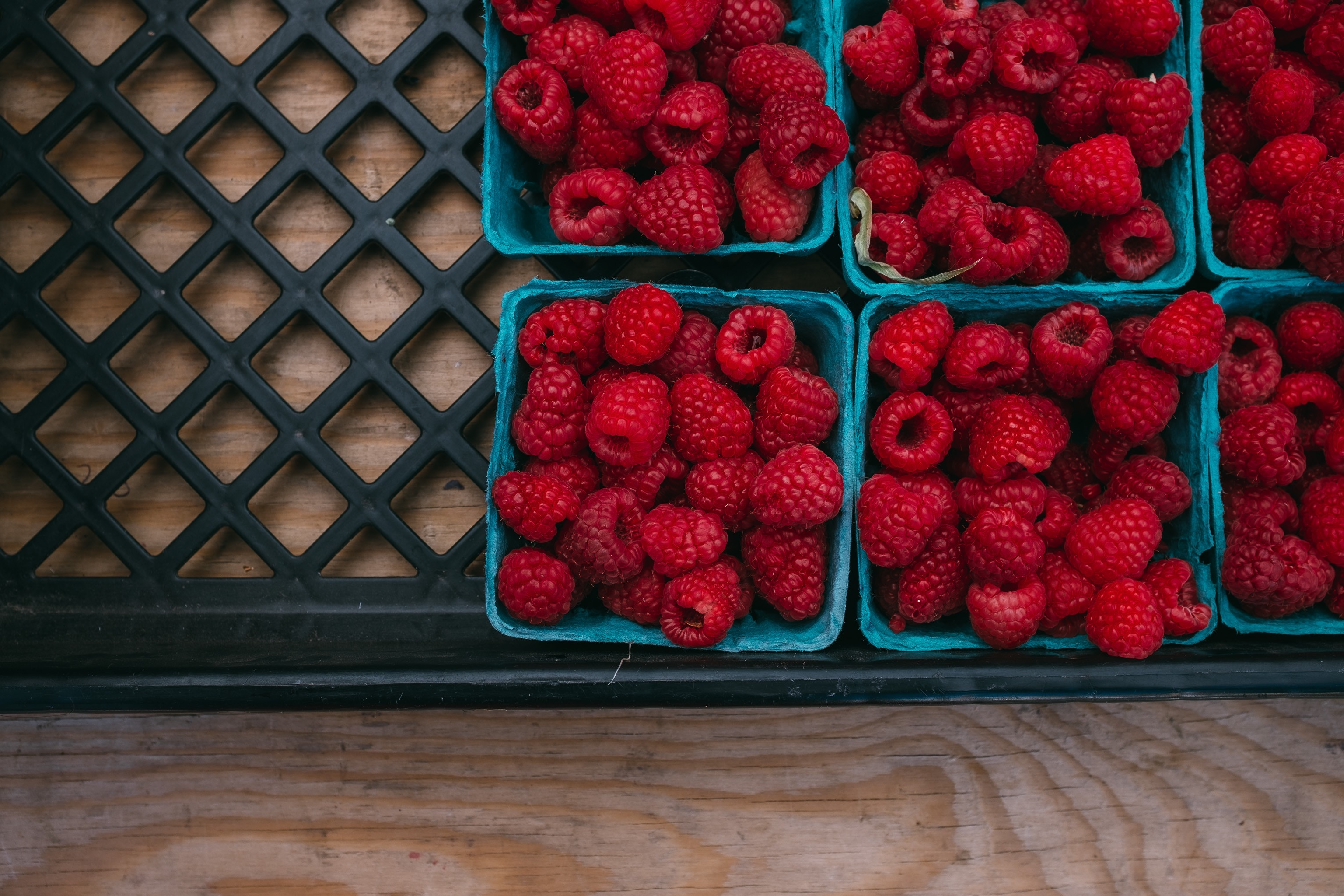 overview of 4 small baskets of raspberries