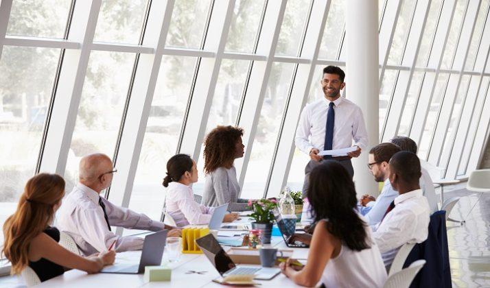 Hispanic Businessman Leading Meeting At Boardroom Table
