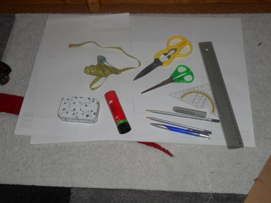 Schere, Papier für Vorlage, Lineal ggfs. inkl. Geodreieck, ggfs. Pritt-Stift zum Papier zusammenfügen, wenn es zu klein ist, Nadel (in der Box), Bleistift oder Kugelschreiber zum Konturen abmalen, Maßband zum Ausmessen