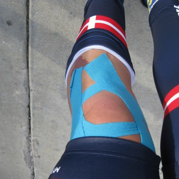 athlete wrapped knee with kinesio tape