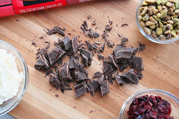 ingredients for dark chocolate bark with cranberries, pistachios, and toasted coconut flakes